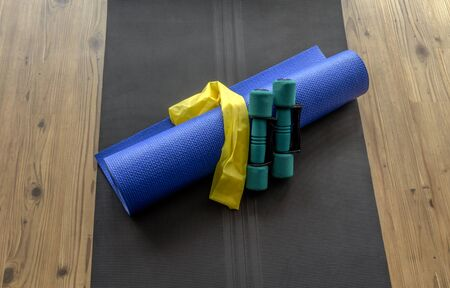 hand weights: Hand weights, resistance band, and yoga mat on black foam mat on wooden floor background