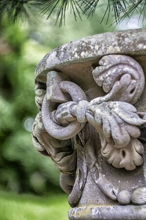 urn: Close up of ancient ornate stone urn with shallow depth of field giving lovely green bokeh background