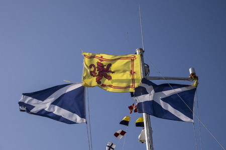 rampant: Royal Standard of Scotland with its red rampant lion on yellow background between two Scottish saltire flags with the cross of Saint Andrew of white and blue Stock Photo