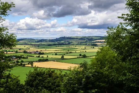 patchwork quilt: North Yorkshire, England - landscape of typical Yorkshire countryside through a frame of trees with patchwork quilt effect fields of green and gold under a cloudy sky Stock Photo