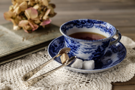 old photograph: Close up of antique blue and white china cup and saucer with tea on lace cloth on wooden table with out of focus faded flower and old photograph album in background