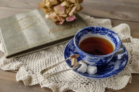 old photograph: Antique blue and white china cup and saucer with tea and sugar cubes on lace cloth on wooden table with out of focus faded flower and old photograph album in background