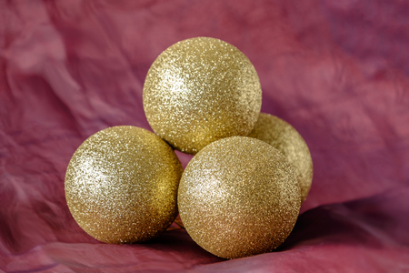 christmas backdrop: Group of four gold glitter baubles for Christmas tree decoration on red cloth backdrop