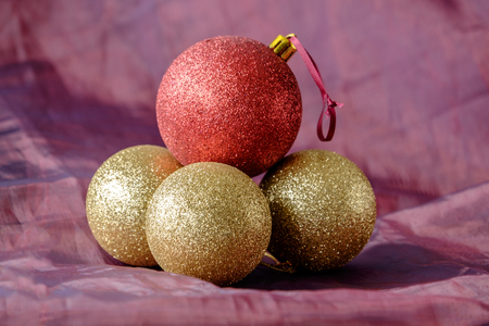 christmas backdrop: Group of bright shiny Christmas tree baubles on red cloth backdrop. Gold glitter baubles with one red balancing on top