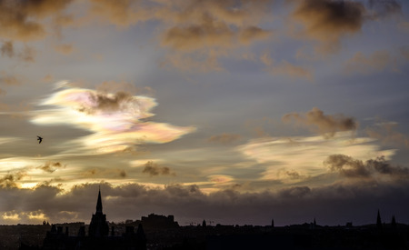 atmospheric phenomena: Rare occurance as nacreous clouds colors the early morning sky in Edinburgh Scotland