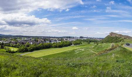 the crags: Panoramic summer view across Holyrood Park with Saisbury Crags looming over Edinburgh Scotland with the Castle on the horizon