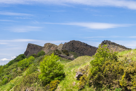 the crags: Man on top of the rugged volcanic rock formations of Salisbury Crags in Edinburgh gives a sense of scale