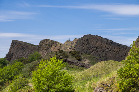 the crags: Rugged ancient volcanic rock formations of Salisbury Crags in Edinburgh Scotland in summer with blue sky Stock Photo