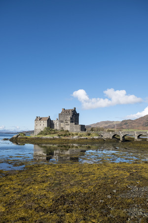 kyle: Popular tourist destinantion of Eilean Donan Castle Scotland, beautiful 13th century fortification at Dornie, Kyle of Lochalsh in the Scottish Highlands with clear blue sky and reflections