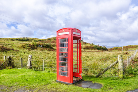 Red telephone box without a door in a remote rural location on the Isle of Skye Scotland