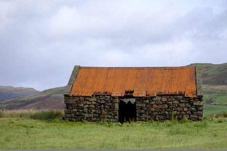 outhouse: Derelict old stone built farm outhouse with red corrugated roof exposed to the elements in a field in the remote countryside of the Isle of Skye Scotland with heather covered hills in the background Stock Photo
