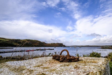 rusting: Beautiful bay in Isle of Skye Scotland with small boats, rugged coastline and concrete block with rusting mooring ring in foreground Stock Photo