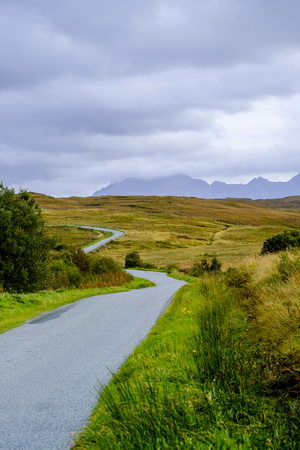 carriageway: A narrow single track road winds throuth the beautiful barren landscape of Isle of Skye Scotland with the peaks of Cuillin mountain range reaching into the clouds on the horizon