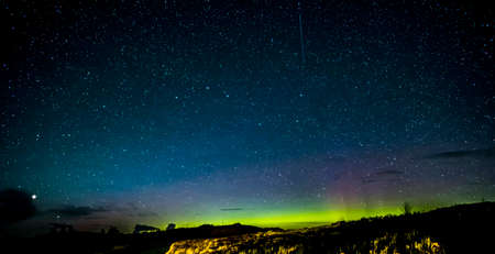brightest: Looking northwards in the Isle of Skye Scotland to the beautiful colors of the night sky showing thousands of stars, satellites and the Northern Lights, Aurora Borealis. Big Dipper or Plough constellation in the center while the brightest star in the bott