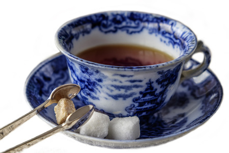 english breakfast tea: Antique blue and white china cup and saucer of black English breakfast tea with silver tongs for white and brown sugar cubes. Isolated on white background with copy space.