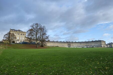 Autumnal scene of the impressive sweep of Georgian architecture of Royal Crescent in Bath, England with cloudy sky and fallen leaves on grass