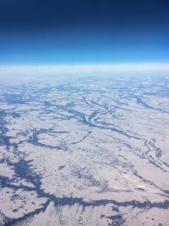 expanse: Aerial view of Northern Canada taken from flight over the vast expanse of frozen rivers and snowy landscape