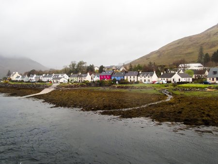 Scottish scene in the rain and mist. The beautiful small former fishing village of Dornie on the shore of Loch Alsh and Loch Duich with its colorful houses and cottages and mountain backdop