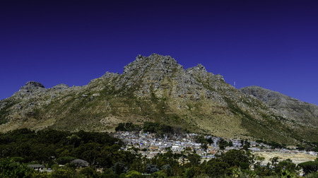 Crowded slums of Imizamo Yethu township,  an informal settlement at Hout Bay Cape Town South Africa against the backdrop of beautiful mountains and blue sky