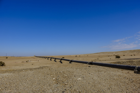 Remote Namib Desert with above ground iron pipe stretching across to carry water from desalination plant in Swakopmund to uranium mine. Built with Chinese investment in belt and road initiative. Stock Photo - 102525697