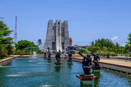 Accra, Ghana - 11 April-2018: Kijkend door waterfonteinen in Kwame Nkrumah Memorial Park naar het marmeren Mausoleum en gouden standbeeld aan de Ghanese president Redactioneel