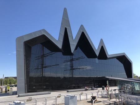 GLASGOW, SCOTLAND – JULY 07 2018: Modern architecture of stunning glass building of award winning Riverside Museum of transport with restored Victorian tall ship Glenlee reflected against blue sky 新聞圖片
