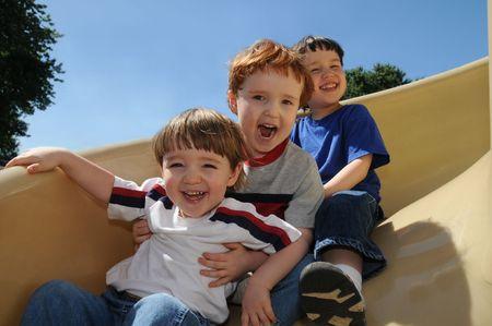 children playground: Tres hermanos tienen un tiempo gran deslizamiento hacia abajo de una diapositiva de espiral en un patio de barrio  Foto de archivo