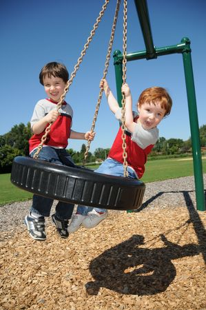 summer tire: Two brothers have fun swinging on a tire swing at a neighborhood park. Stock Photo