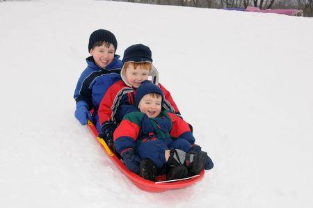 Three preschool-aged boys have fun together sliding downhill on a pleasant winter day. photo