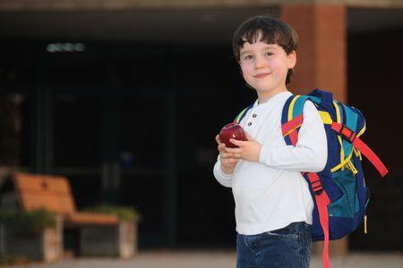 mochila escolar: Un ni�o de primer grado se detiene y sonr�e en su camino a la escuela para el primer d�a de clase