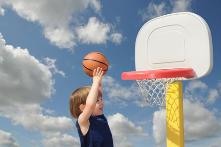 outdoor basketball court: A little boy reaches up to put his basketball in the hoop, confident of his success Stock Photo
