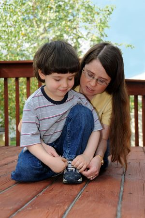 shoelaces: A mother teaches her preschool boy how to tie his shoes Stock Photo