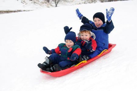 sledding: Three preschool-aged boys have fun together sliding downhill on a pleasant winter day.