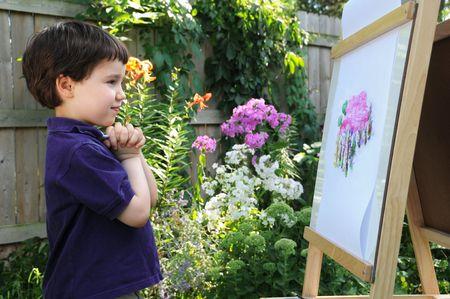 小さな男の子は彼の隣に花園に見られるフロックスの彼の絵画を賞賛します。