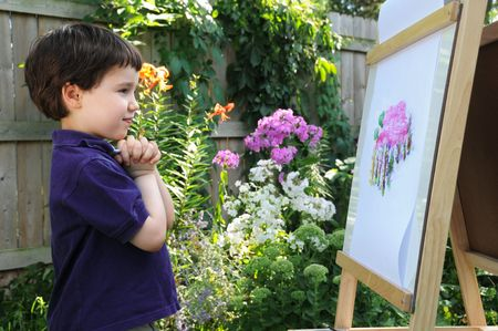 A little boy admires his painting of a phlox seen in the flower garden next to him