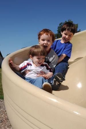 ni�os jugando en el parque: Tres hermanos disfrutan juntos de deslizamiento hacia abajo de una diapositiva de espiral en un patio de recreo de barrio
