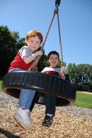 tire: Two brothers having fun swinging on a tire swing at a neighborhood park. Stock Photo