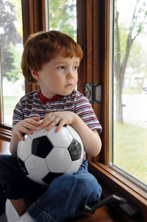 A little boy sits by a window on a rainy day, wishing he could go outside and play soccer photo