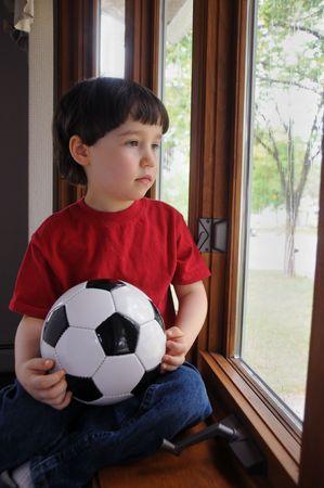Een kleine jongen zit door een venster op een regenachtige dag, die hij kon naar buiten gaan en spelen voet bal