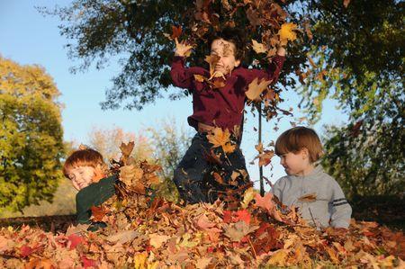 in a pile: Tres hermanos romp en las hojas ca�das en una soleada tarde de oto�o