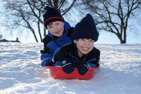 Two little boys have fun together sliding downhill on a pleasant winter day. photo