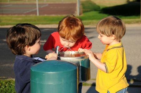 Three brothers take turns drinking water from a drinking fountain at a neighborhood park.