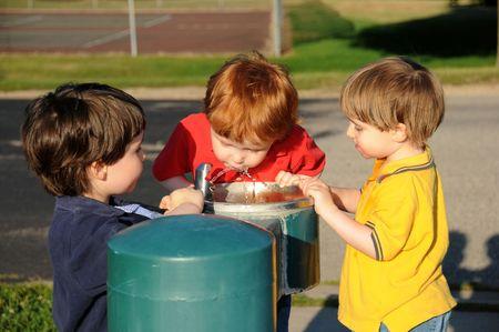 tomando refresco: Tres hermanos toman turnos bebiendo agua de una fuente de potable en un parque del barrio.