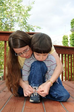 teaches: A mother teaches her preschool boy how to tie his shoes Stock Photo