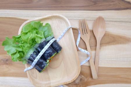 plato del buen comer: Un plato de ensalada con una línea de medición sobre un fondo blanco. Concepto de salud y salud.