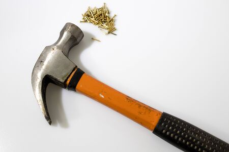 Hammer and gold tacks in a white background