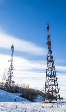 Telecommunication tower in a blue sky and clouds