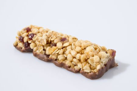Cereal bar  whit fruit and chocolate in a white background composition