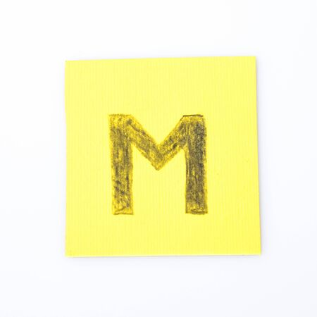 M alphabet letter handwrite on a yellow paper composition