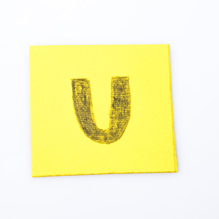 U alphabet letter handwrite on a yellow paper composition